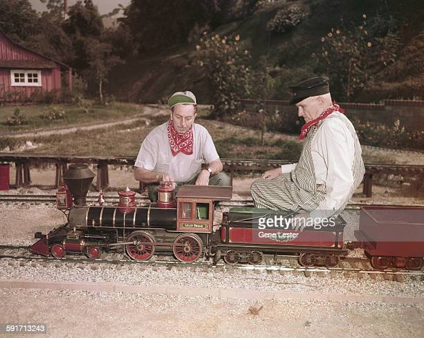 American movie producer artist and animator Walt Disney and an unidentified engineer look over the Lilly Bell Disney's scale model functional steam...