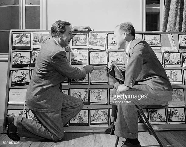 American movie producer artist and animator Walt Disney and musician Johnny Mercer look at story boards from Disney's 'Soug of the South' movie...