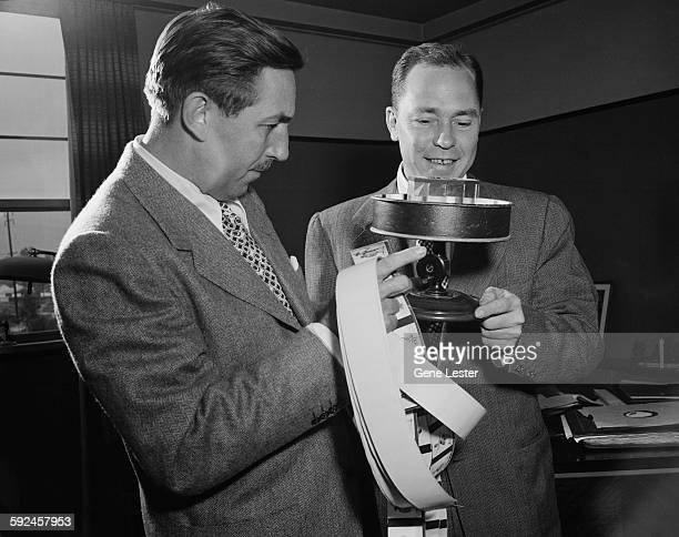 American movie producer artist and animator Walt Disney and musician Johnny Mercer look a handcrank animation projector called a praxinoscope October...