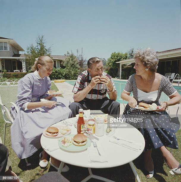 American movie producer artist and animator Walt Disney eats a hamburger with his wife Lillian and one of their daughters as they all sit at a...