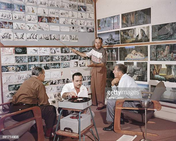 American movie producer artist and animator Walt Disney listens to an unidentified animator talk through the storyboards for the film 'Sleeping...