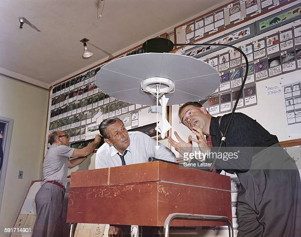 American movie producer artist and animator Walt Disney listens to animator Ward Kimball talk about a model for a television project California 1950s...