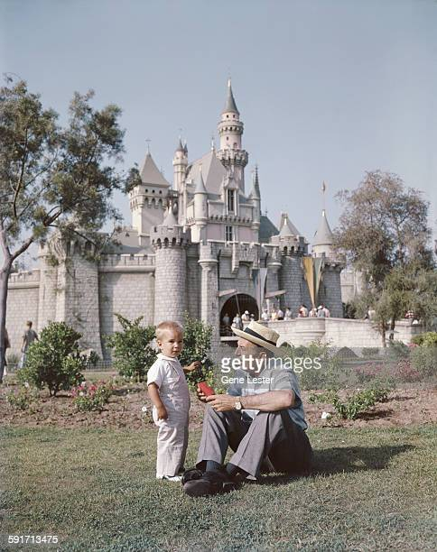 American movie producer artist and animator Walt Disney sits with one of his grandsons on the lawn in front of the Disneyland castle Anaheim...