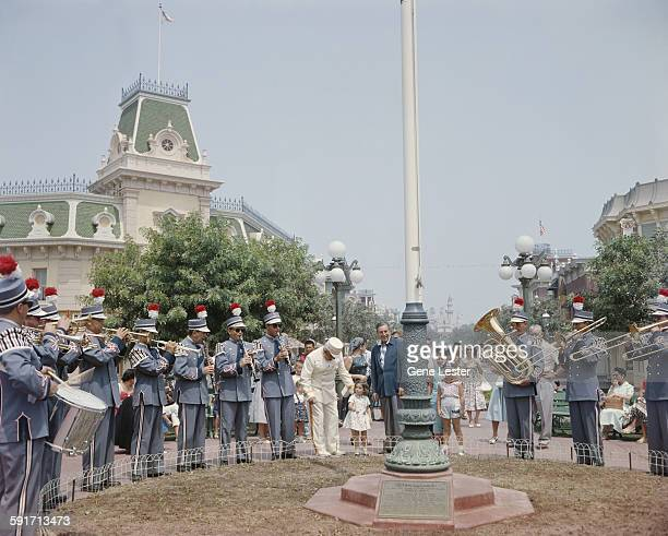 American movie producer artist and animator Walt Disney stands with a brass band and attendees at his Disneyland amusement park Anaheim California...