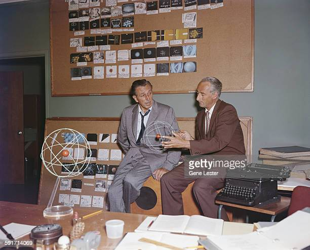 American movie producer artist and animator Walt Disney talks to an unidentified collegue who holds a model of an atom California 1950s