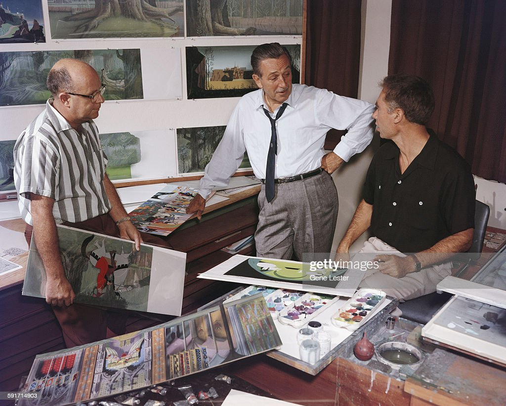 American movie producer, artist, and animator Walt Disney (1901 - 1966) (center) talks with a pair of unidentified animators about some of their work, California, 1950s.