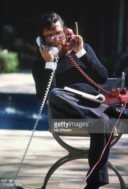 American movie producer Robert Evans sits poolside on two telephones in garden of his Beverly Hills home in california, circa 1978: