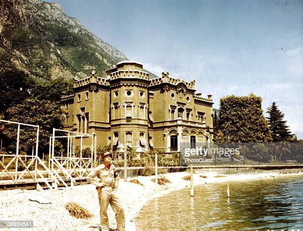 American MP Private First Class Verlin A Larson with 150th MP Company of the US 15th Army stands at the water's edge in front of a villa named...