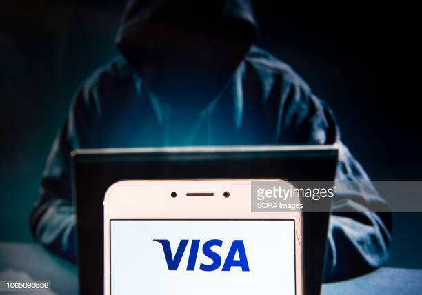 American multinational financial services corporation and payment system Visa Inc logo is seen on an Android mobile device with a figure of hacker in...