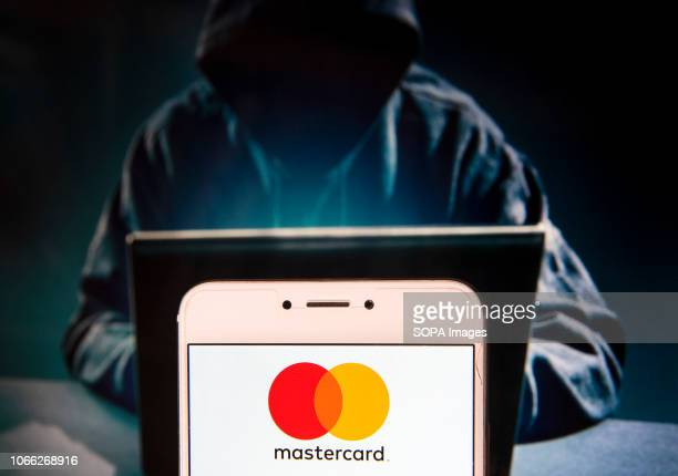 American multinational financial services corporation and payment system Mastercard logo is seen on an Android mobile device with a figure of hacker...