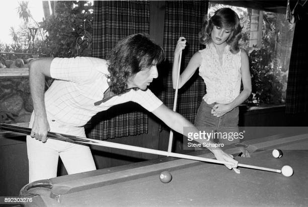 American musician Alice Cooper lines up a shot as he plays pool with his wife American choreographer Sheryl Cooper watches Los Angeles California 1978
