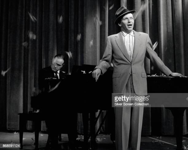 American musician and actor Frank Sinatra , accompanied by Bob Hope on piano, performs during rehearsals for the debut episode of 'The Frank Sinatra...