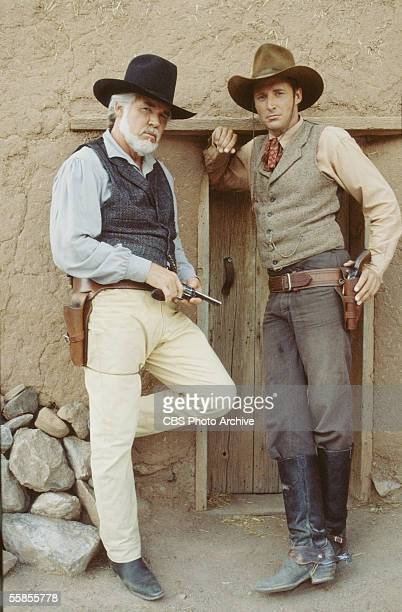 American musician and actor Kenny Rogers holds a pistol in his hand as he stands in character as Brady Hawkes next to colleague and compatriot Brue...