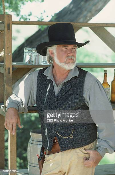 American musician and actor Kenny Rogers leans on a shelf with glasses and bottles in a publicity photo for the CBS television movie 'The Gambler...