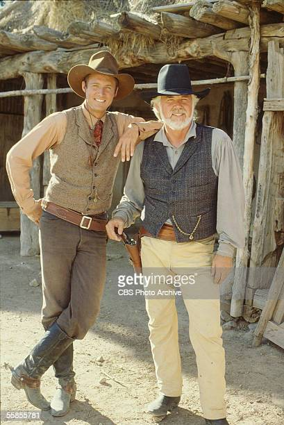American musician and actor Kenny Rogers rests his hand on his pistol and stands next to colleague and compatriot Brue Boxleitner as they pose for a...