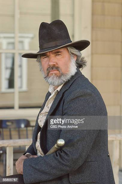 American musician and actor Kenny Rogers sits and holds a walking stick in a publicity photo for the CBS television movie 'The Gambler,' directed by...