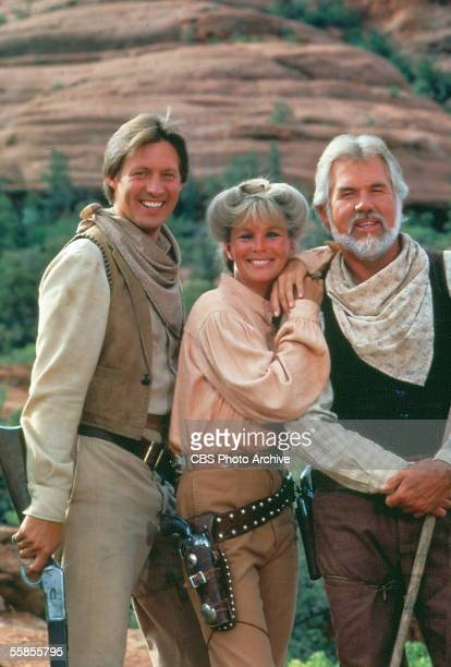 American musician and actor Kenny Rogers stands and holds a walking stick alongside colleagues and compatriots Bruce Boxleitner and Linda Evans in a...