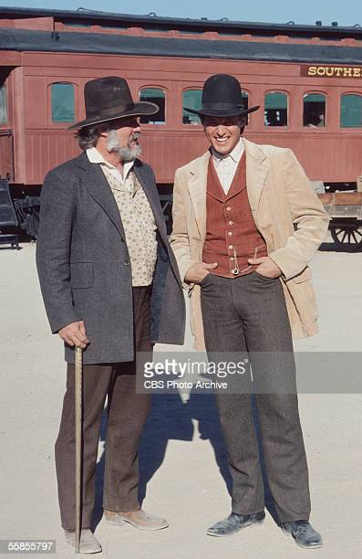 American musician and actor Kenny Rogers stands and holds a walking stick alongside colleague and compatriot Bruce Boxleitner in a publicity photo...