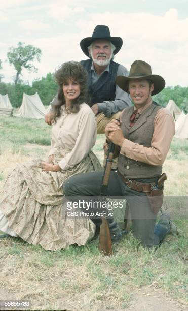 American musician and actor Kenny Rogers stands behind colleagues and compatriots Brue Boxleitner and Linda Gray as they pose for a publicity photo...