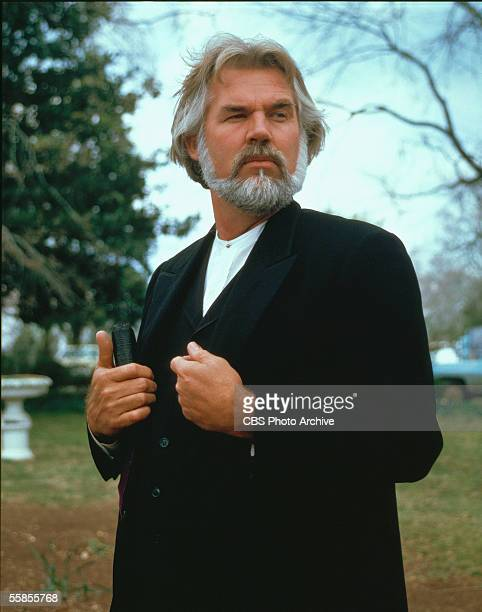 American musician and actor Kenny Rogers stands with a book in costume as Uncle Matthew Spencer in a publicity portrait for the CBS television movie...
