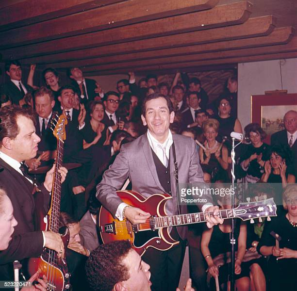 American musician and actor Trini Lopez performs live on stage playing a Gibson Barney Kessel sunburst Custom guitar at a club in Paris in 1964