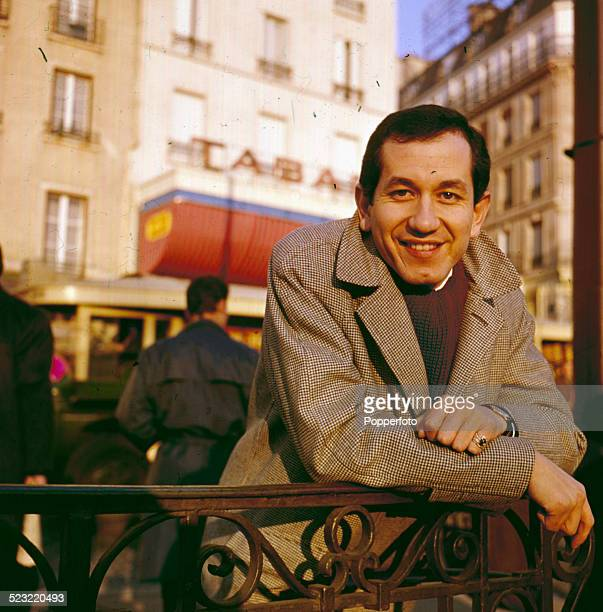 American musician and actor Trini Lopez pictured standing outside a hotel in Paris in 1964