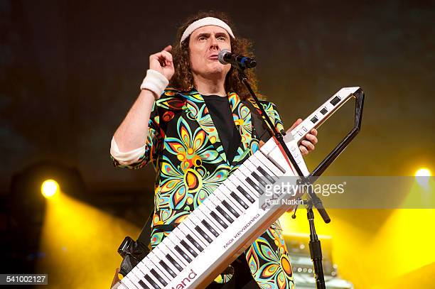 American musician and comedian Weird Al Yankovic in a brightly colored jacket plays a keyboard as he performs onstage at the Star Plaza Theater...