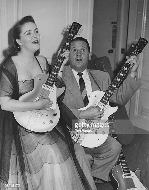 American musician and inventor Les Paul and his wife Mary Ford demonstrate two of Paul's new electric guitars during a press reception at the Savoy...