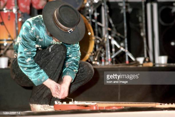 American musician and lead singer Stevie Ray Vaughan of the group Stevie Ray Vaughan and Double Trouble, fixes his guitar on stage during the Soul to...
