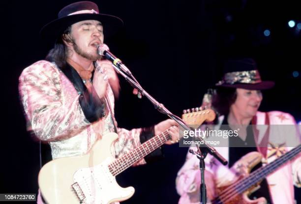 American musician and lead singer Stevie Ray Vaughan of the group Stevie Ray Vaughan and Double Trouble, plays on stage with American bass guitarist...