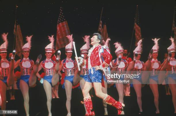 American musician and performer Liberace prances onto the stage in sequined short shorts in front of a kick line of the Rockettes Radio City Music...