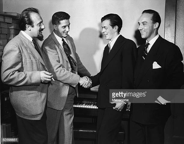 American musician and producer Mitch Miller looks on as American record producer musician and music critic John Hammond shakes hands with an...