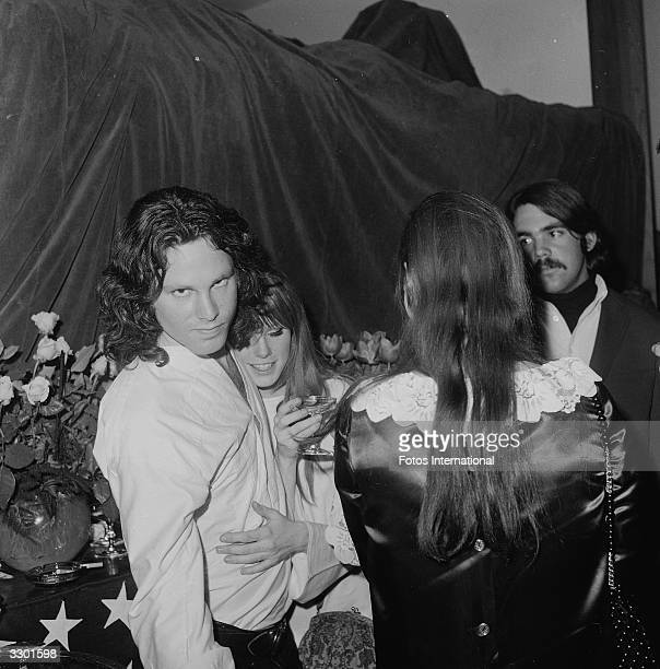 American musician and singer Jim Morrison and Pamela Courson embrace at the opening of 'The Beard' at the Warner Playhouse California January 24 1968