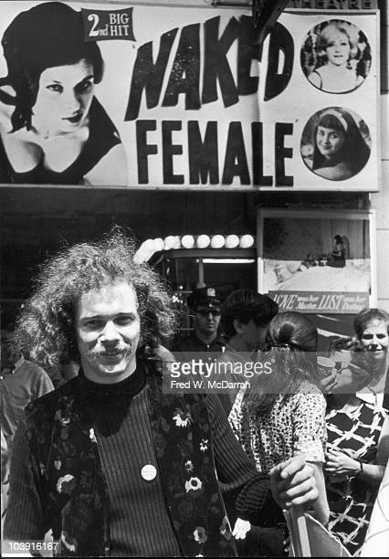 American musician author and activist Ed Sanders smiles has he poses under a poster that advertises the film 'Naked Female' New York New York August...