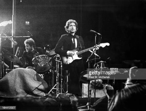 American musician Bob Dylan plays guitar on stage with Levon Helm on drums at Madison Square Garden New York New York January 30 1974