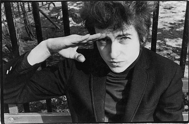 American musician Bob Dylan salutes as he sits on a...
