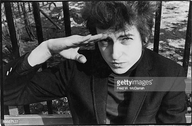 American musician Bob Dylan salutes as he sits on a bench in Sheridan Square Park New York New York January 22 1965