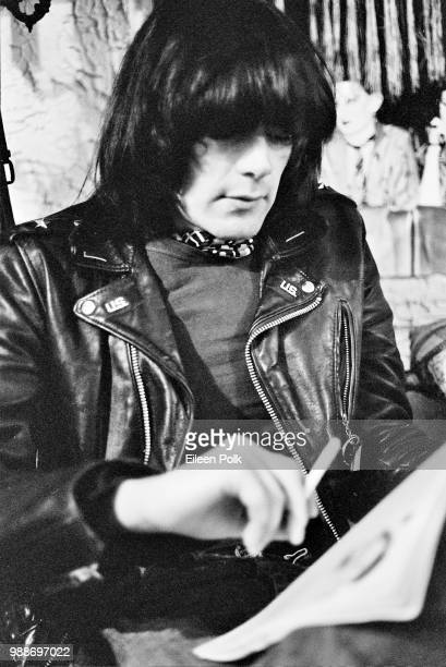 American musician Dee Dee Ramone of the punk group Ramones smokes as he reads a magazine in the clothing store Revenge New York New York 1977