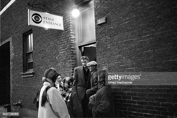 Alfred Wertheimer/Getty Images American musician Elvis Presley signs autographs for fans at the CBSTV Studio 50 stage door New York New York March 17...