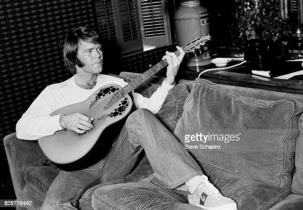 American musician Glen Campbell play guitar as he reclines on a couch in his home Los Angeles California 1978