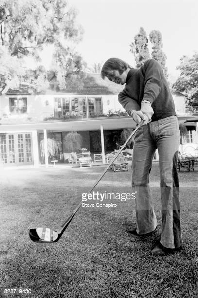 American musician Glen Campbell practices his golf swing outside his home, Los Angeles, California, 1978.