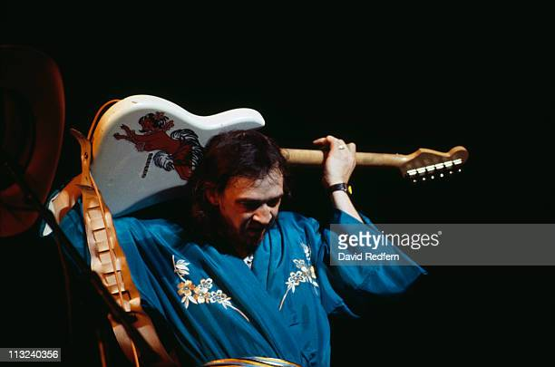 American musician, guitarist and singer Stevie Ray Vaughan performs live on stage playing a Fender Stratocaster guitar behind his head during a...