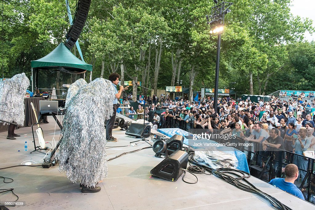 American musician Helado Negro (born Roberto Carlos Lange) performs onstage, with costumed dancers, during a concert at the 16th Annual Latin American Music Conference (LAMC) series at Central Park SummerStage, New York, New York, July 8, 2015.