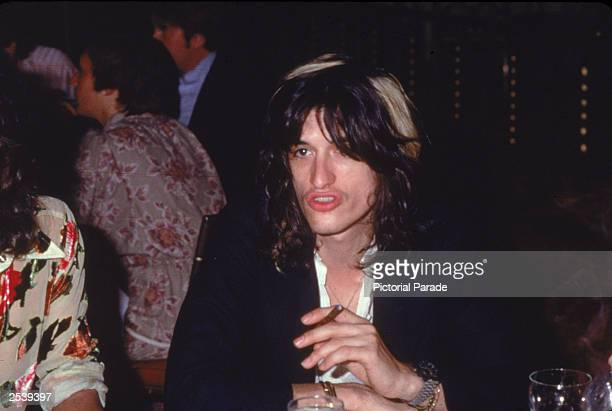 American musician Joe Perry of Aerosmith sits at a table during a luncheon for the film 'Sgt Pepper's Lonely Hearts Club Band England 1978