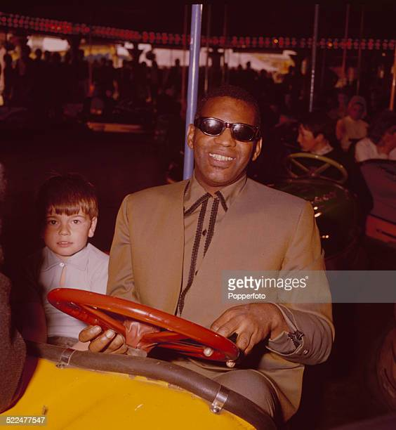 American musician Ray Charles pictured in a dodgem car with child actor Piers Bishop co star of the film Ballad in Blue at Battersea Pleasure Gardens...