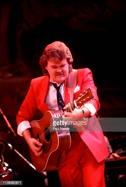 American musician Ricky Skaggs plays guitar as he performs onstage at the Rosemont Horizon Rosemont Illinois November 30 1984