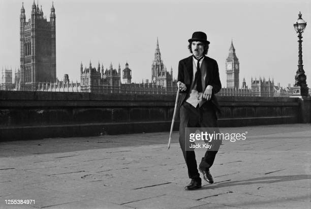 American musician Ron Mael of Sparks on the Albert Embankment London dressed as Charlie Chaplin's 'Tramp' character 1972 In the background is the...