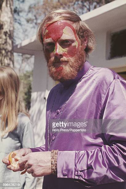 American musician, singer and founder member of the Beach Boys, Mike Love pictured with red and green face paint and wearing a purple shirt at the...