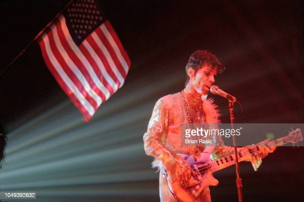 American musician singer and guitarist Prince performs live on stage in front of a stars and stripes flag during a 'The Ultimate Live Experince' tour...