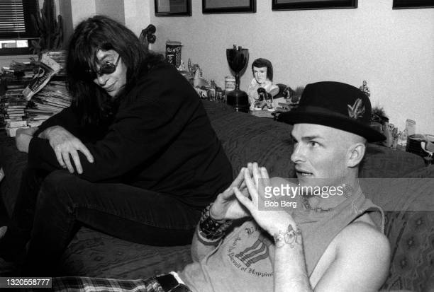 American musician, singer, composer, and lead vocalist Joey Ramone sits on the couch with American Grammy Award-winning musician, singer, songwriter,...